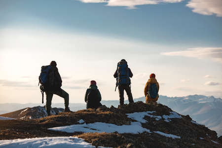 Four hikers are relaxing on mountain top