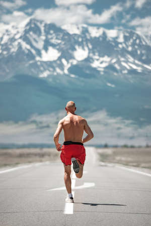 Athletic jogger runs by straight mountain road