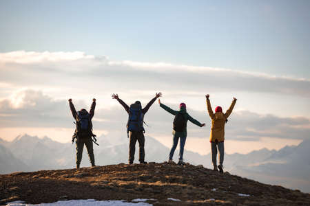 Four young tourists with backpacks in winner poses at mountain top