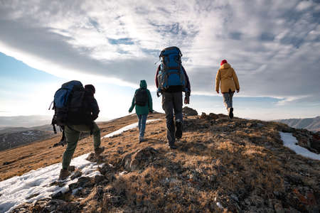 Group of diverse tourists or hikers walks on mountain top Фото со стока
