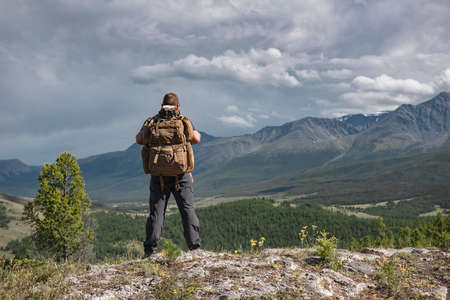 Hiker stands with backpack on background of mountains