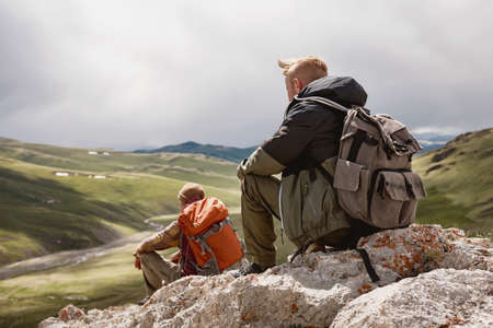 Two hikers sit and relax in mountains