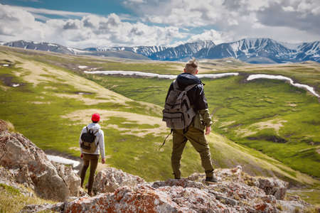 Two hikers with small backpacks enjoys the view