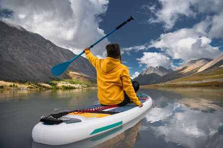 Stylish girl in yellow hoodie walks on sup board at the white mountain lake. Supboarding concept