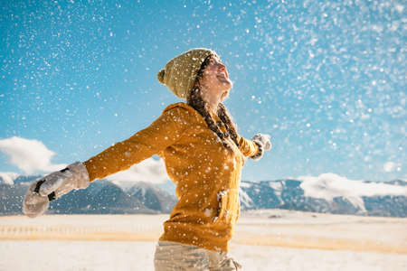 Young happy stylish girl whirls with raised hands and enjoys the snow in mountains. Winter holidays concept