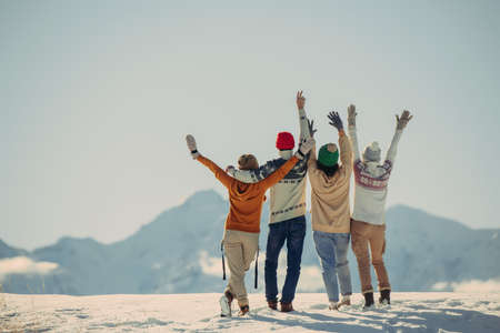 Four happy stylish friends stands, embrace and looks at snow capped mountains. Winter vacations concept