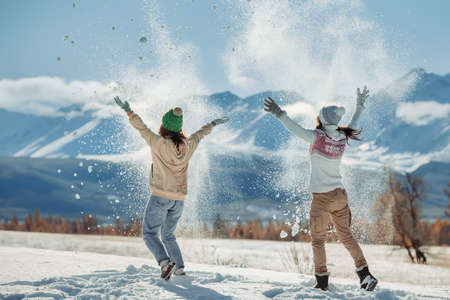 Two happy young girls are having fun and tossing snow in mountains. Winter holidays concept Standard-Bild