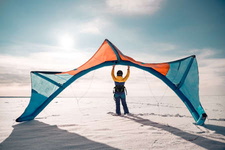 Sporty girl stands and hold snowkite in hands. Winter kitesurfing concept