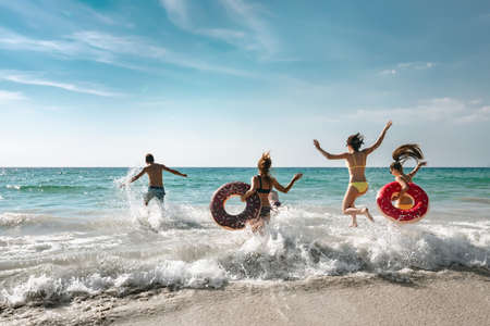 Happy cheerful friends resting on a beautiful beach at sunny day and running into the sea with inflatable rings. Tropical vacations concept