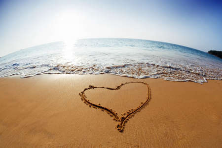 Seashore with waves and draw a heart in the sand Standard-Bild