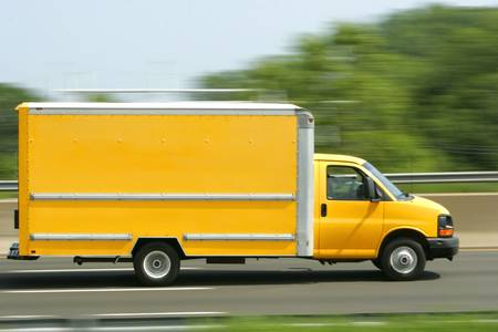 A bright yellow truck van speeds down the highway. Copy space on side of van. Stock Photo