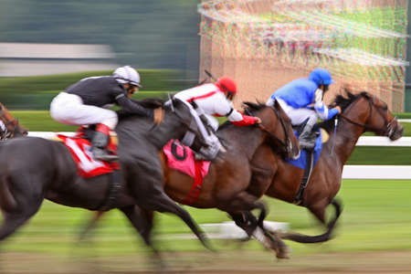 Slow shutter speed rendering of three racing jockeys and thoroughbreds photo