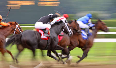 speed race: Slow shutter speed rendering of jockeys and horses racing the final furlong to the finish line Stock Photo