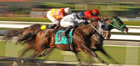 Slow shutter speed rendering of several racing horses and jockeys.
