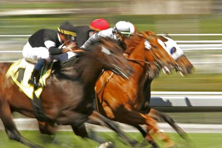 Slow shutter speed rendering of a group of racing jockeys and horses 스톡 콘텐츠