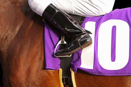 Close up of jockeys leg in stirrup with purple saddlecloth on horse. Banco de Imagens