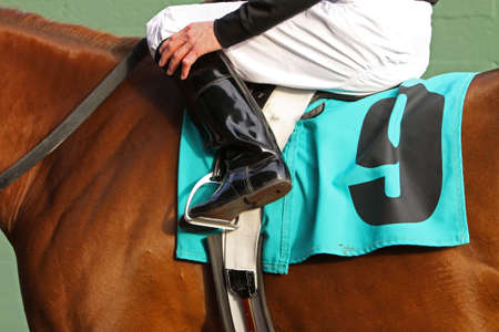 Close up of jockey sitting in saddle of thoroughbred race horse. Focus on boot and stirrup. Stock Photo
