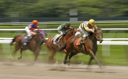 Slow shutter speed rendering of racing horses and jockeys photo
