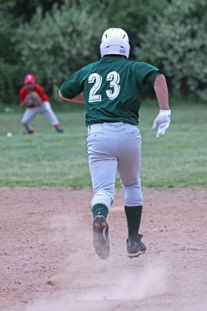 shortstop: A youth baseball player runs to second base, trying to beat the throw. Nicely blurred shortstop fielding the ball in background.