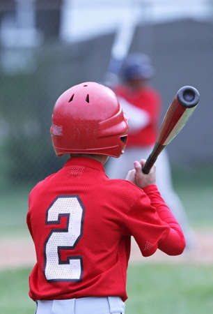 A Little League baseball player waches his teammate as he waits his turn to bat in the on deck circle.