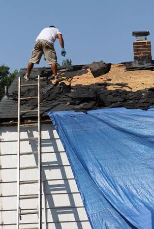 toiture maison: Couvreur retirer les vieux bardeaux un toit de la maison. Banque d'images