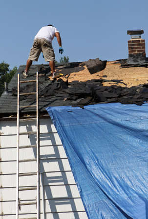 Roofer removing old shingles from a house roof.