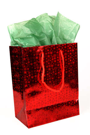 tissue paper: Red shiny Christmas gift bag with green tissue on white.