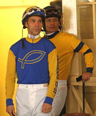 alberto: ARCADIA, CA - 16 de febrero: jinetes Thoroughbred Alberto Delgado (izquierda) y Sa�l Arias esperan en el paddock para sus caballos para la primera carrera en el hist�rico parque de Santa Anita el 16 de Feb de 2014 en Arcadia, California. Editorial