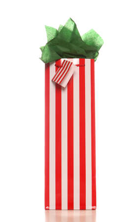 uncluttered: Red and white striped Christmas wine gift bag with bright green tissue and gift tag. White background with soft shadow.