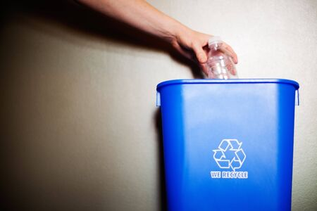 Woman's arm dropping plastic bottling into recycling container Archivio Fotografico