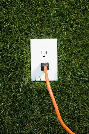 plugged: Electrical outlet in grass with extension cord plugged in