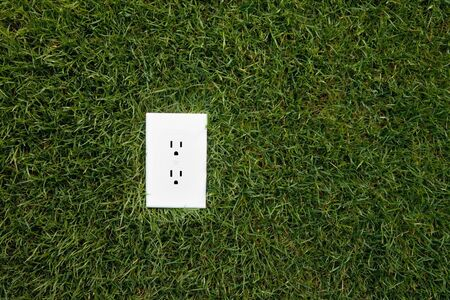 Electrical outlet in grass, alternative energy source Stock Photo