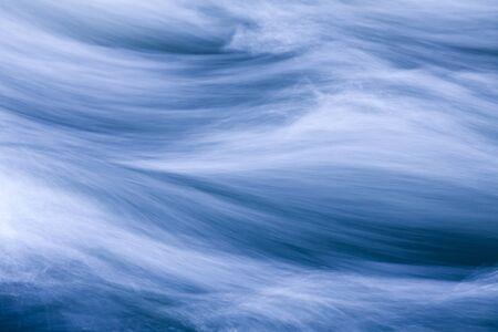 Rushing water in a river, toned blue Foto de archivo