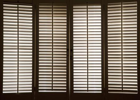 Fensterläden aus Holz vor der hellen, sonnendurchfluteten Fenstern Standard-Bild - 12275249