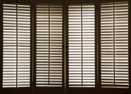 shutter: Wooden shutters in front of bright, sunlit windows Stock Photo
