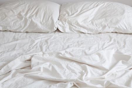 Puste łóżko z rozczochrany poduszki i przeÅ›cieradÅ'a Zdjęcie Seryjne