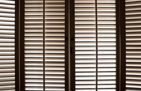 Wooden shutters in front of bright, sunlit windows Foto de archivo