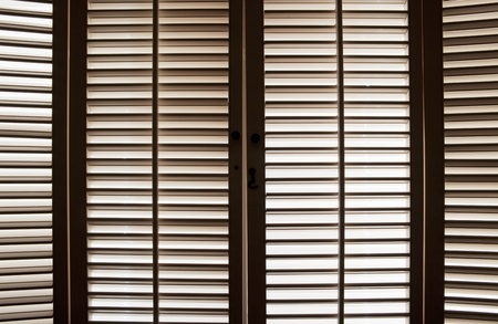 Wooden shutters in front of bright, sunlit windows Stock Photo