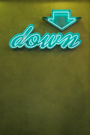 Neon down arrow sign, Seattle, Washington  Stock photo of a neon down arrow sign on a green wall with copy space  photo