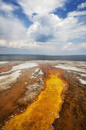 runoff: Colorful runoff from Black Pool leads to Yellowstone Lake, Yellowstone National Park, Wyoming