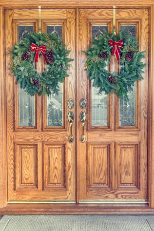 Two Christmas wreaths hanging from a double front door photo