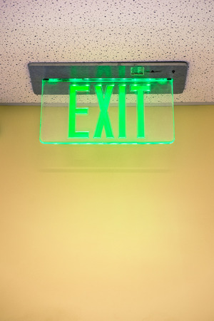 A lit exit sign hanging from the ceiling in an office building. photo