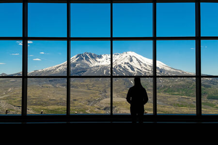 Woman standing in silhouette in front of a picture window at Mount St. Helens National Monument photo