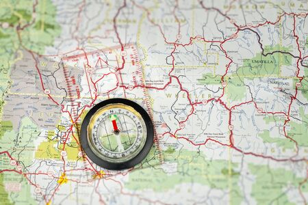 brujula: A aguja de la brújula al norte mientras está acostado en una hoja de ruta Foto de archivo