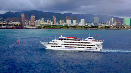 A sunset dinner cruise ship as it enters Honolulu Harbor on Oahu