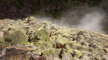 vents: Steam rising from vents between colorful boulders in Hawaii Volcanoes National Park Stock Photo