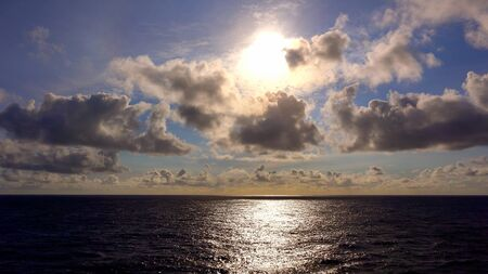 away from it all: View of the setting sun and clouds as it sets over the Pacific Ocean from a cruise ship at sear near Hawaii Stock Photo
