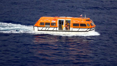 lifeboat: A cruise ship tender aka lifeboat returning to the ship full of tourists on Hawaii Editorial