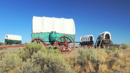 A covered wagon train forms a protective circle to camp along the Oregon Trail in eastern Oregon Stok Fotoğraf - 46182870
