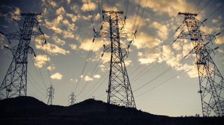 infraestructura: líneas de alta tensión y torres de energía en silueta contra el cielo puesta de sol y nubes Foto de archivo